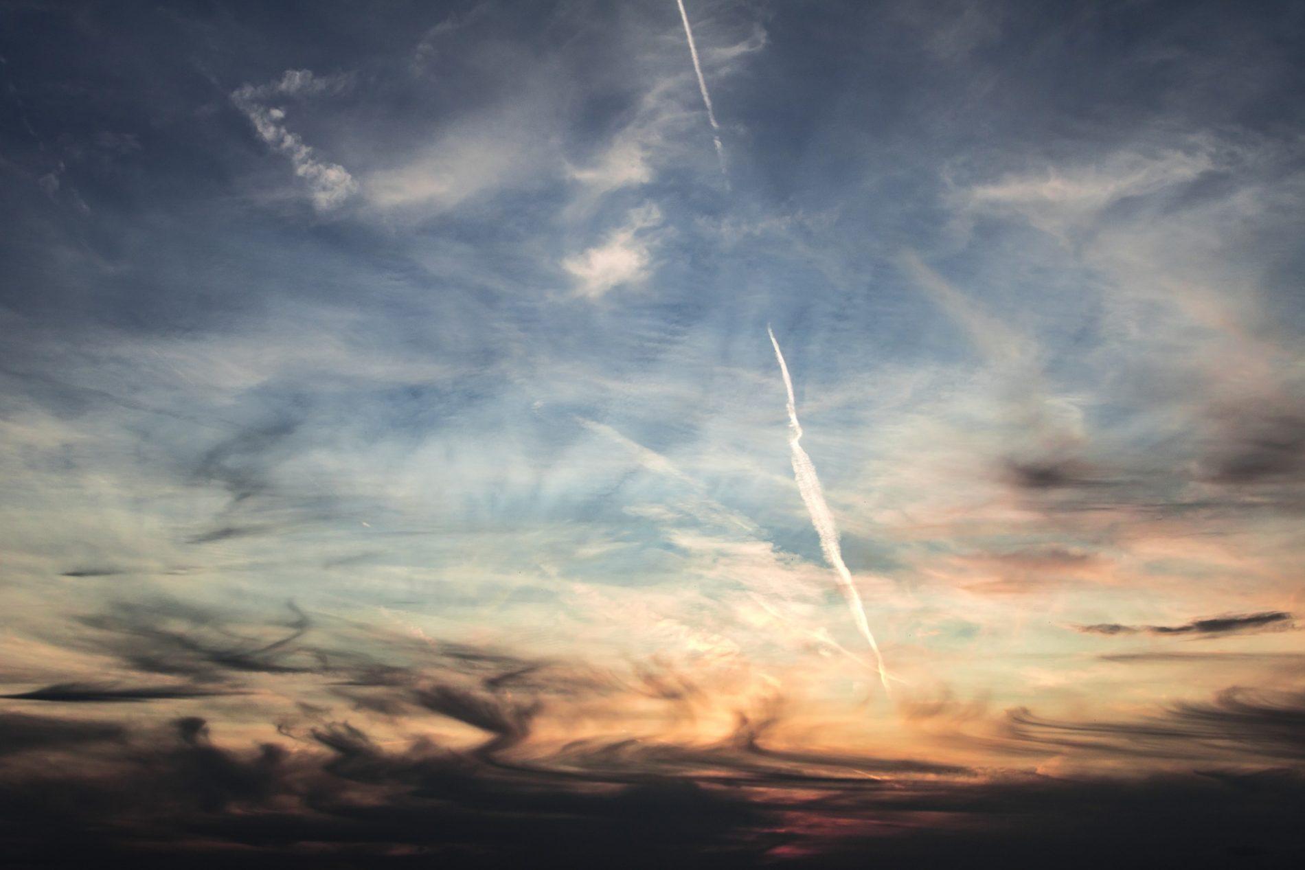 Der Sonnenuntergang am Himmel wird durchzogen von Kondensstreifen