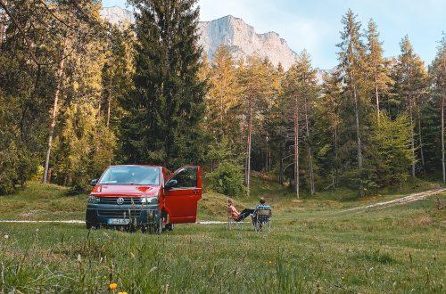 Franziska und Felix mit ihrem selbst ausgebauten VW T5 vor einer Bergkulisse in Berchtesgaden.