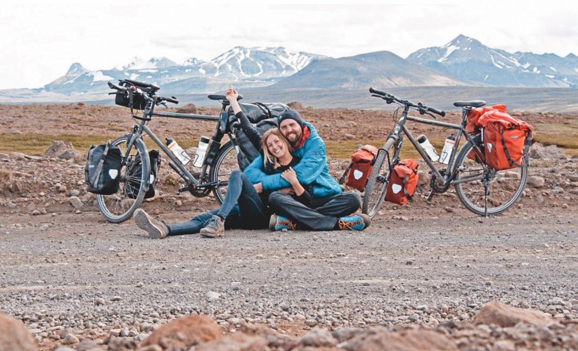 Franziska und Felix mit ihren Fahrrädern im isländischen Hochland. Im Hintergrund Bergkulisse
