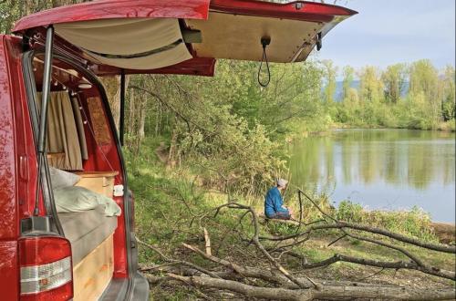 Felix sitzt vor unserem selbst ausgebauten VW T5 Bus Willi an einem See im Chiemgau