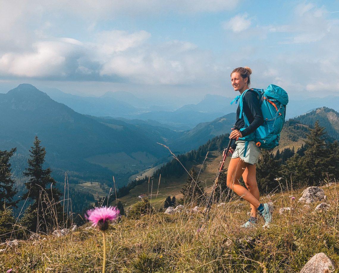 Franziska wandert über eine Blumenwiese im Chiemgau, Bergkulisse im Hintergrund.